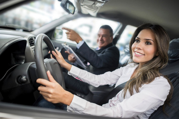 Woman buying a car and testing it with salesman